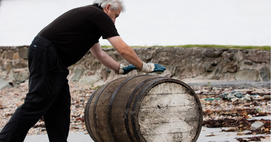 Man pushing barrels of rare whiskies across beach.